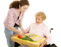 young lady serving a food to an old woman